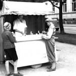 Kaksi pikkupoikaa ostavat jäätelöä valkoasuiselta jäätelönmyyjältä.